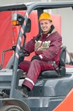 Warehouse worker driver in. Young smiley warehouse worker driver in uniform driving forklift stacker Royalty Free Stock Images