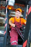 Warehouse worker driver in forklift. Young cheerful warehouse worker driver in uniform driving forklift stacker loader Stock Image