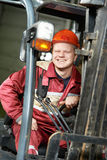 Warehouse worker driver in forklift. Young cheerful warehouse worker driver in uniform driving forklift stacker loader Royalty Free Stock Photography