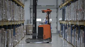 Warehouse worker driver in uniform loading cardboard boxes by forklift stacker loader furnirure storage boards