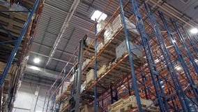 Warehouse worker driver in uniform loading cardboard boxes by forklift stacker loader furnirure storage boards. Warehouse worker driver in uniform loading stock video