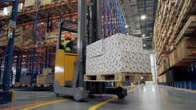 Warehouse worker driver in uniform loading cardboard boxes by forklift stacker loader furnirure storage boards. Warehouse worker driver in uniform loading stock footage