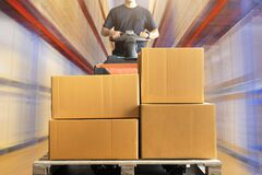 Free Warehouse Worker Driving Electric Forklift Pallet Jack Unloading Shipment Pallet Good Royalty Free Stock Image - 181794236