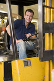 Warehouse worker in forklift. Warehouse worker driving a yellow forklift Royalty Free Stock Photography