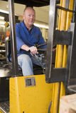 Warehouse worker in forklift. Warehouse worker driving a yellow forklift Stock Photos