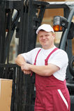 Warehouse worker in front of forklift Royalty Free Stock Photography