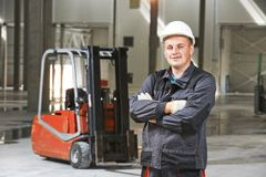 Warehouse worker in front of forklift Stock Photography