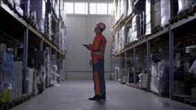 Warehouse worker with glasses in hard helmet and uniform makes notes on tablet during carries out an audit