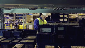 Warehouse worker going along shelves and writing