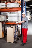 Warehouse Worker With Handtruck Loading Cardboard Royalty Free Stock Photography