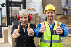 Warehouse worker and his manager giving thumbs up Stock Photo