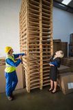 Warehouse worker and his manager looking stack of pallet Stock Images