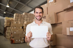 Warehouse worker holding blank board. Portrait of warehouse worker holding blank board in warehouse Royalty Free Stock Image
