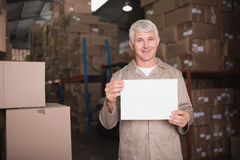 Warehouse worker holding blank board. Portrait of warehouse worker holding blank board in warehouse Stock Image