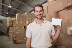 Warehouse worker holding blank paper. Portrait of warehouse worker holding blank paper in warehouse Stock Photo