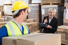 Warehouse worker holding box with manager behind him Royalty Free Stock Photo