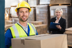 Warehouse worker holding box with manager behind him Stock Photography