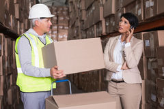 Warehouse worker holding box with manager on a call. In a large warehouse Stock Photo