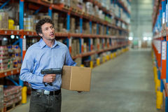 Warehouse worker holding cardboard box and barcode scanner machine Royalty Free Stock Photography