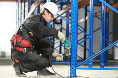 Warehouse worker installing rack arrangement Royalty Free Stock Photo