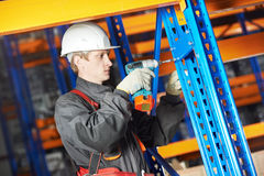 Warehouse worker installing rack arrangement. One warehouse worker in uniform with power tool drilling hole during rack arrangement erection work Royalty Free Stock Photography