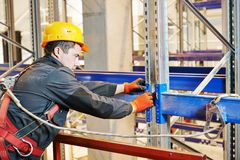 Warehouse worker installing rack arrangement Royalty Free Stock Photo