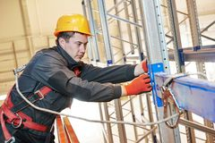 Warehouse worker installing rack arrangement. One warehouse worker in uniform during rack erection work installation Royalty Free Stock Photography