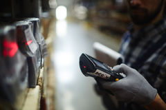 Warehouse Worker Inventorying Stock. Side view closeup of bar code scanner in hand of unrecognizable warehouse worker doing inventory of stock stock images