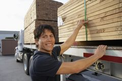 Warehouse Worker Loading Wooden Planks On Truck Carrier. Portrait of a happy middle aged warehouse worker loading wooden planks on truck carrier Royalty Free Stock Photography