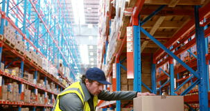 Warehouse worker looking at package. In warehouse 4k