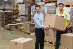 Warehouse worker and manager carrying a box together Royalty Free Stock Photos