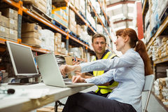 Warehouse worker and manager looking at laptop Stock Photos