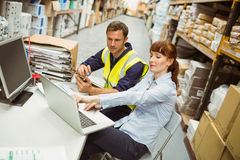 Warehouse worker and manager looking at laptop Stock Photo