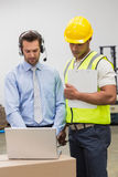 Warehouse worker and manager looking at laptop Royalty Free Stock Image