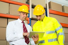 Warehouse Worker And Manager Looking At Laptop Royalty Free Stock Photos