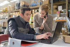 Warehouse worker and manager looking at laptop in warehouse stock images