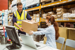 Warehouse worker and manager passing a box Stock Photography