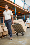 Warehouse worker moving boxes on trolley Stock Photos