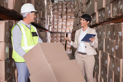 Warehouse worker moving boxes on trolley talking to manager Stock Photos