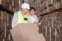 Warehouse worker moving boxes on trolley talking to manager Royalty Free Stock Photo