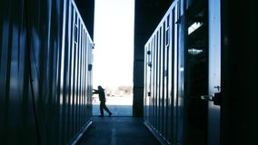 Warehouse worker opening metal door.