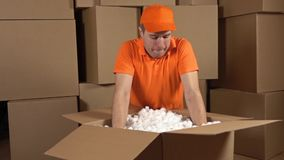 Warehouse worker in orange uniform unboxing big carton full of soft packaging material. Shockproof container. Multiple stock video footage