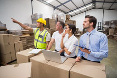 Warehouse worker pointing something to his colleagues Stock Images
