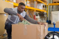 Warehouse worker preparing shipment in large warehouse. Warehouse worker preparing a shipment in a large warehouse Royalty Free Stock Photo
