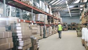 Warehouse worker protection equipment walks by warehouseinspects the goods for shipment stock video footage