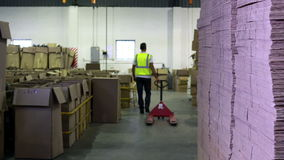Warehouse worker pulling trolley away form camera stock footage