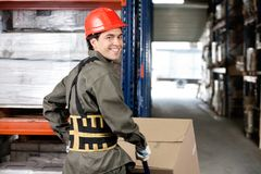 Warehouse Worker Pushing Handtruck With Cardboard Stock Image