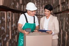 Warehouse worker scanning box with manager holding tablet pc. In a large warehouse Royalty Free Stock Image
