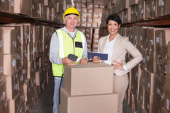 Warehouse worker scanning box with manager holding tablet pc. In a large warehouse Royalty Free Stock Photography