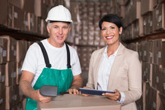 Warehouse worker scanning box with manager holding tablet pc. In a large warehouse Stock Image
